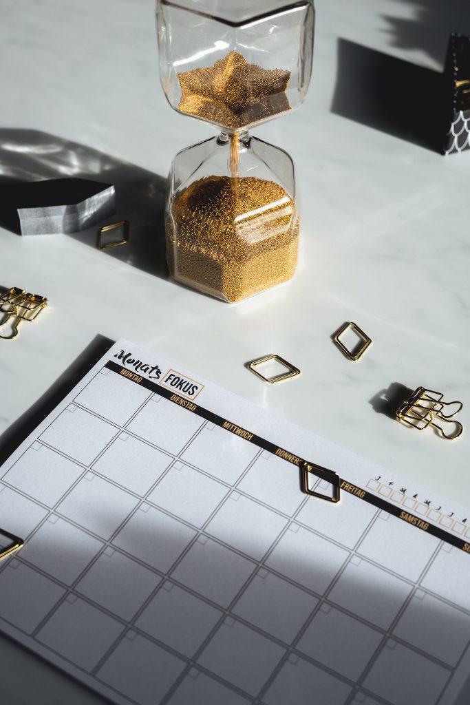 Goldene Sanduhr neben Kalender für Zeitmanagement als Soft Skill in der Selbstständigkeit