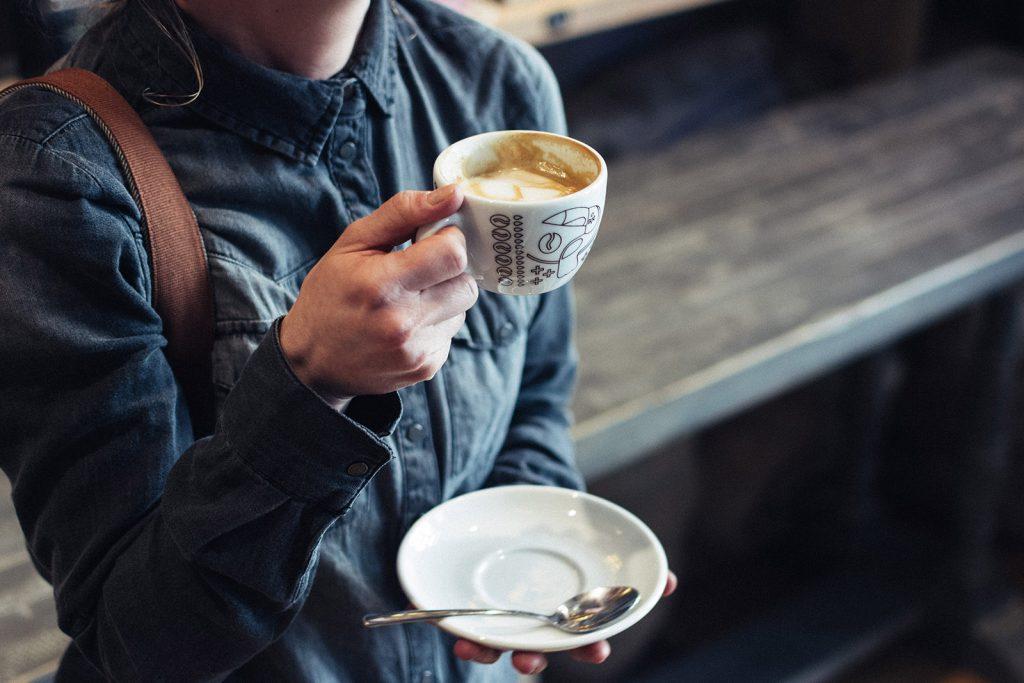 Freelancer in Café mit WLAN zum Arbeiten mit Kaffeetasse