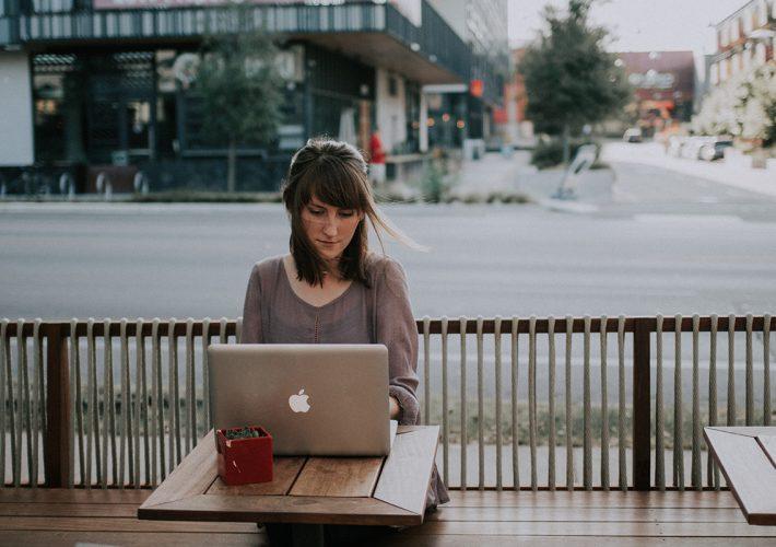 Freelancerin mit Laptop in Café für Selbstständigkeit