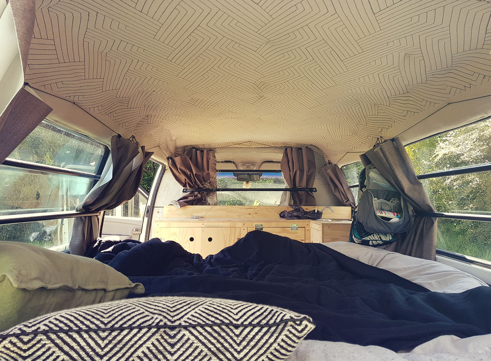 Camper eingerichtet von innen mit Kissen und Bettwäsche