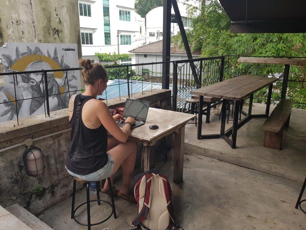 Frau an Laptop auf Dachterrasse