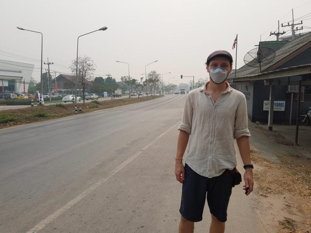 Mann mit Atemmaske an Hauptstraße mit Smog in Thailand