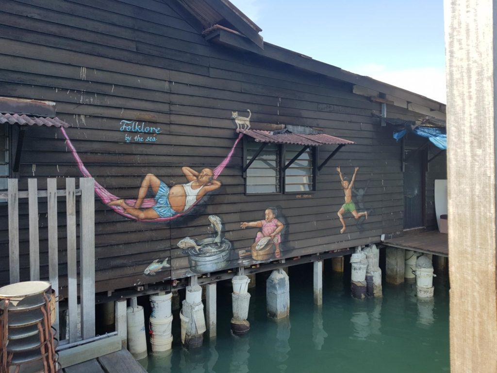 Familie in Hängematte an Hauswand Street Art